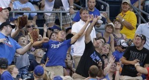 Fans try to catch a fly foul ball hit by Oakland Athletics' Seth Smith during the fifth inning Friday in Kansas City. (AP Photo/Charlie Riedel)