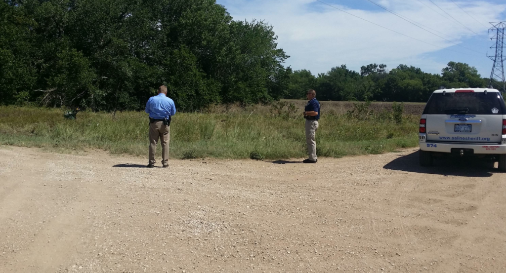Law enforcement authorities search the tree line for a suspect on Monday afternoon in Saline County