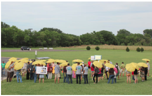 Participants in a June 23 rally  hold umbrellas to protest a proposal by Westar to make solar customers pay a higher monthly flat fee. photo by ANDY MARSO