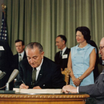 President Lyndon B. Johnson signing the Medicare bill at the Harry S. Truman Library in Independence, Missouri. Former President Harry S. Truman is seated at the table with Johnson. In the background (from left to right) are Sen. Edward V. Long, an unidentified man, Sen. Mike Mansfield, Lady Bird Johnson, Vice President Hubert Humphrey and Bess Truman. CREDIT EXECUTIVE OFFICE OF THE PRESIDENT OF THE UNITED STATES