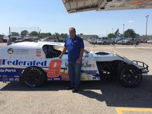 Former NASCAR driver Kenny Schrader stands next to his 1st class chassis IMCA modified race car at Schwan's Friday afternoon (Photo by Terry Tebrugge/Salina Post)