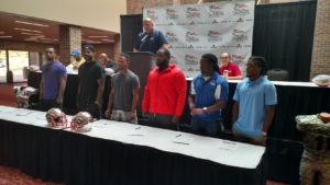 Head Coach Eric Clayton looks on as six new Liberty players sign their contracts Wednesday (Photo by Devin Hanney/Salina Post)
