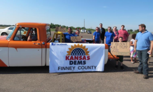 Photo by Lisa Rodriguez/KCUR The Finney County Democrats started meeting in December. With signs in English and Spanish at the Beef Empire Days Parade in Garden City, they were hoping to capture Latino voters' attention.